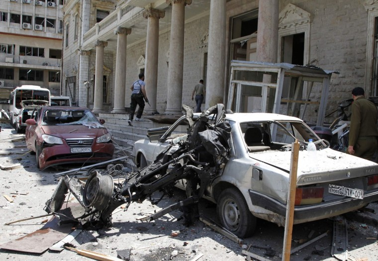 Security personnel walk in front of the former Interior Ministry building after a blast at Marjeh Square in Damascus. The bomb in central Damascus killed 13 people on Tuesday, state television said, a day after Prime Minister Wael al-Halki survived an attack on his convoy in the heart of the Syrian capital. State television said 70 people were wounded, several critically. The British-based Syrian Observatory reported 9 dead civilians and 3 security men and said the death toll was likely to rise. (Khaled al-Hariri/Reuters)