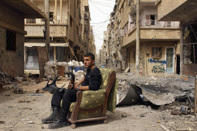 A member of the Free Syrian Army holds his weapon as he sits on a sofa in the middle of a street in Deir al-Zor April 2, 2013. Picture taken April 2, 2013. (Khalil Ashawi/Reuters)