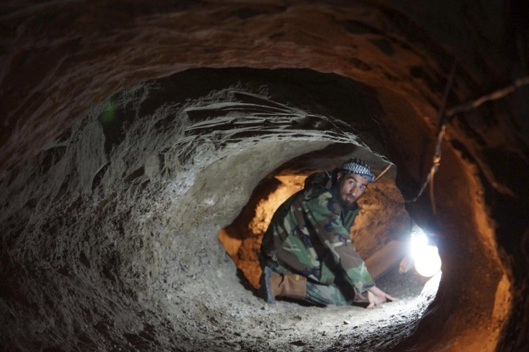 A Free Syrian Army fighter is seen in a tunnel in Deir al-Zor April 6, 2013. The 98-foot tunnel was dug under an area where Syrian Army forces have set up base in Deir Al-Zor, according to members of the Free Syrian Army. (Khalil Ashawi/Reuters)