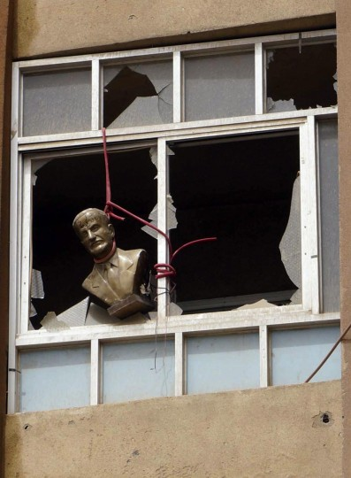 A bust of late Syrian President Hafez al-Assad, father of the current president Bashar al-Assad, is seen hung at a broken window of a building in Deir al-Zor April 2, 2013. (Khalil Ashawi/Reuters)