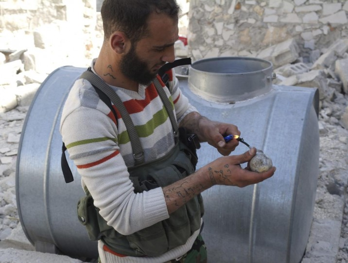 A Free Syrian Army fighter lights up an improvised hand grenade during clashes with forces loyal to Syria's President Bashar al-Assad in Aleppo's neighbourhood of Salaheddine, April 29, 2013. (Ammar Abdullah/Reuters)
