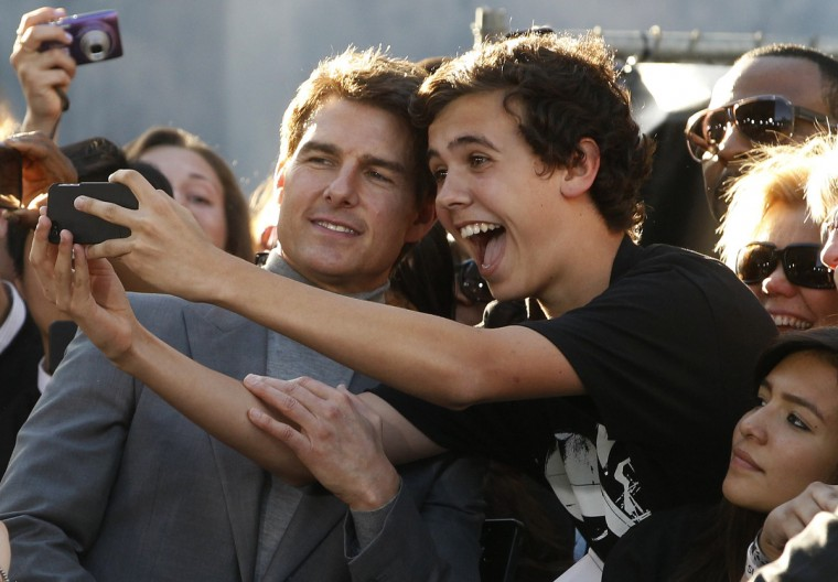 "Actor Tom Cruise, left, poses with fans along Hollywood Boulevard at the premiere of his new film ""Oblivion"" in Hollywood. (Fred Prouser/Reuters photo)"