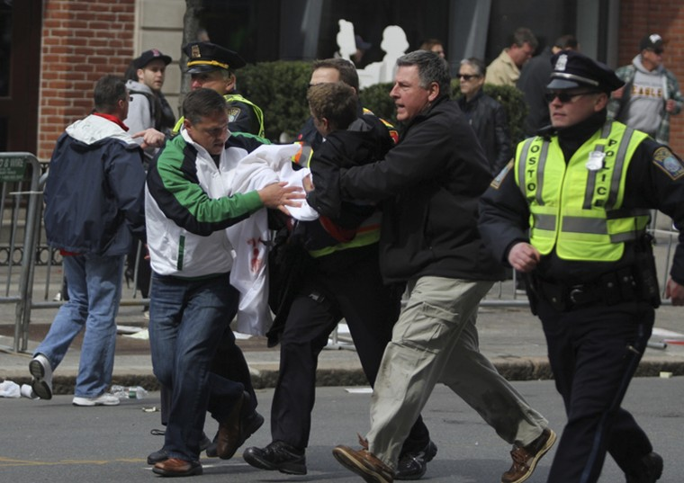 An injured victim is carried from the scene of an explosion at the Boston Marathon in Boston, Massachusetts, April 15, 2013. Two explosions struck the marathon as runners crossed the finish line on Monday, witnesses said, injuring an unknown number of people on what is ordinarily a festive day in the city. (Kenshin Okubo/Reuters photo)
