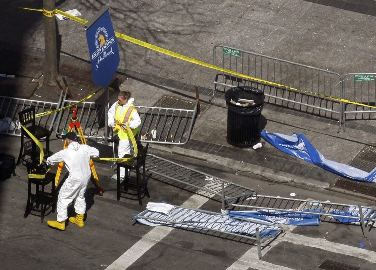 """Officials wrap crime scene tape around an area on Boylston Street a day after two explosions at the Boston Marathon in Boston, Massachusetts April 16, 2013. Two bombs packed with ball bearings tore through crowds near the finish line of the Boston Marathon on Monday, killing three people and triggering a massive hunt for those behind an attack the White House said would be treated as """"an act of terror."""" (Jessica Rinaldi/Reuters photo)"""