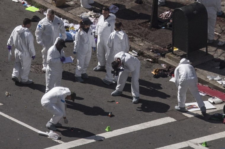 """Investigators survey the site of a bomb blast on Boylston Street a day after two explosions hit the Boston Marathon in Boston, Massachusetts April 16, 2013. A pressure cooker stuffed with gunpowder and shrapnel caused at least one of the blasts at the Boston Marathon that killed three people and injured 176 others in the worst attack on U.S. soil since September 11, 2001, law enforcement sources said on Tuesday. President Barack Obama called the two bombings on the marathon finish line an """"act of terror"""" and police said parts of the center of Boston could be closed for days as they investigated the blasts that caused several people to lose limbs. (Adrees Latif/Reuters)"""