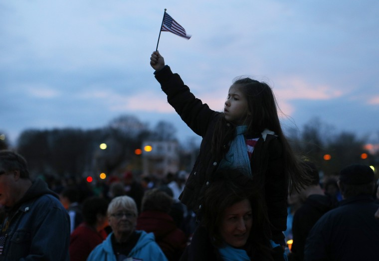 """A girl holds up a U.S. flag during a candlelight vigil in the Dorchester neighborhood of Boston, Massachusetts April 16, 2013 where eight-year-old Boston Marathon bombing victim Martin Richard lived. A Little League baseball player, Martin lived in the blue Victorian house in working-class Dorchester - a Boston neighborhood dotted with """"Kids at Play"""" traffic signs and budding trees - with his parents Bill and Denise, sister Jane, 7, and brother Henry, 10. Bill Richard told the world in an email on Tuesday that his son had been killed when bombs exploded at the marathon finish line. Martin's mother and sister were seriously injured. (Brian Snyder/Reuters photo)"""