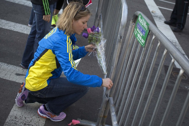 """Alison Gardner lays flowers at the barricaded entrance at Boylston Street near the finish line of the Boston Marathon in Boston, Massachusetts April 16, 2013. Two bombs packed with ball bearings tore through crowds near the finish line of the Boston Marathon, killing three people and triggering a massive hunt for those behind an attack the White House said would be treated as """"an act of terror."""" (Shannon Stapleton/Reuters photo)"""