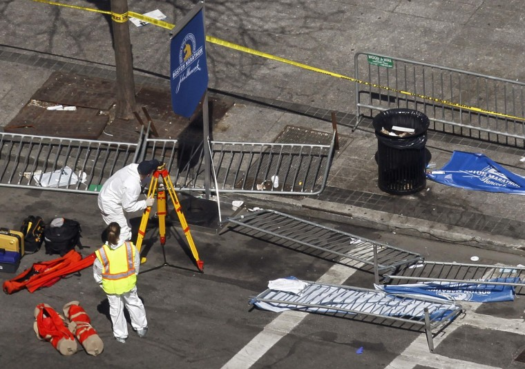 """Officials survey the damage on Boylston Street a day after two explosions at the Boston Marathon in Boston, Massachusetts April 16, 2013. Two bombs packed with ball bearings tore through crowds near the finish line of the Boston Marathon on Monday, killing three people and triggering a massive hunt for those behind an attack the White House said would be treated as """"an act of terror."""" (Jessica Rinaldi/Reuters photo)"""