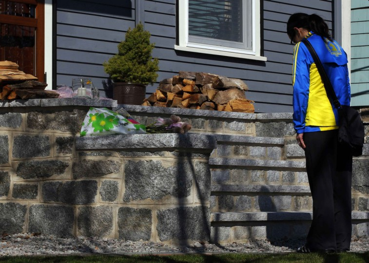 Boston Marathon runner Megan Cloke pauses after leaving flowers on the door step of eight-year-old Martin Richard's home in the Dorchester neighborhood in Boston, Massachusetts April 16, 2013. News reports say that Martin Richard was one of the victims of two explosions which hit the Boston Marathon as runners crossed the finish line on Monday killing at least three people and injuring over 100 others. (Brian Snyder/Reuters photo)