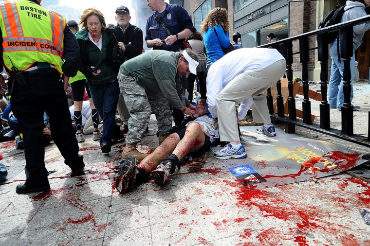 A wounded spectator is cared for following an explosion at the Boston Marathon in Boston, Massachusetts, April 15, 2013. Two simultaneous explosions ripped through the crowd at the finish line of the Boston Marathon on Monday, killing two people and injuring dozens on a day when tens of thousands of people pack the streets to watch the world famous race. (MetroWest Daily News/Ken McGagh/Reuters)
