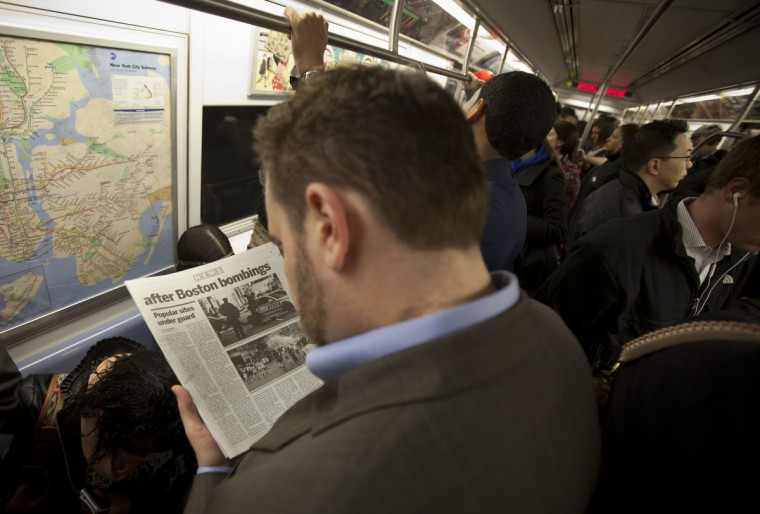 """A commuter reads about the events in Boston on a subway train in New York, April 16, 2013. Two bombs packed with ball bearings tore through crowds near the finish of the Boston Marathon, killing three people and triggering a massive hunt for those behind an attack the White House said would be treated as """"an act of terror"""". (Carlo Allegri /Reuters photo)"""