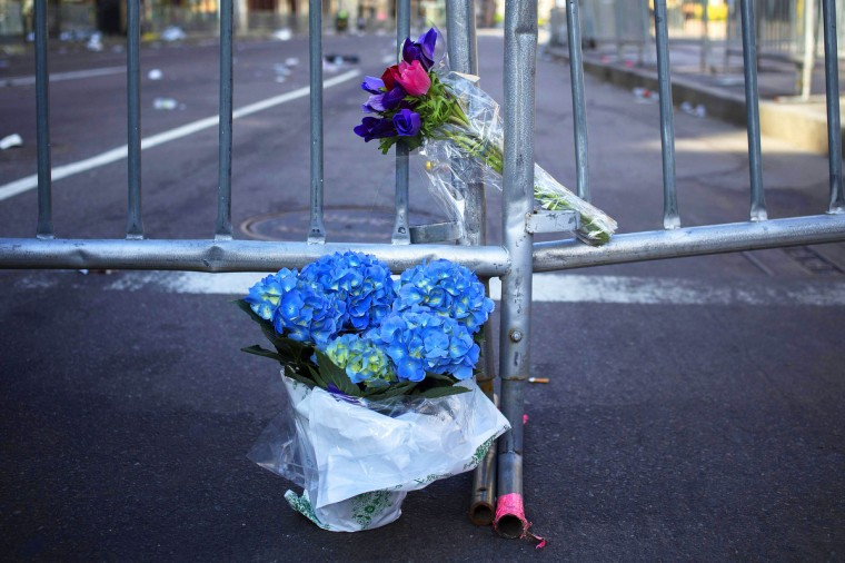 """Flowers are seen at the barricaded entrance at Boylston Street near the finish line of the Boston Marathon in Boston, Massachusetts April 16, 2013. Two bombs packed with ball bearings tore through crowds near the finish line of the Boston Marathon, killing three people and triggering a massive hunt for those behind an attack the White House said would be treated as """"an act of terror."""" (Shannon Stapleton/Reuters photo)"""