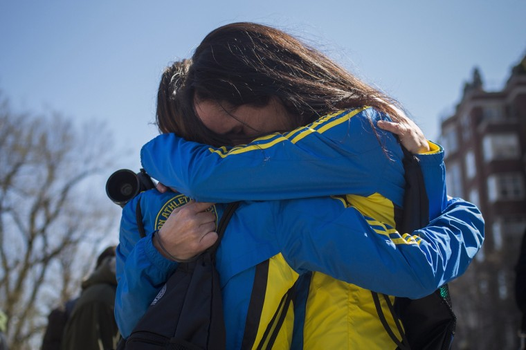 """Boston Marathon runners Lisa Kresky-Griffin and Tammy Snyder (L) embrace at the barricaded entrance at Boylston Street near the finish line of the Boston Marathon in Boston, Massachusetts April 16, 2013. Two bombs packed with ball bearings tore through crowds near the finish line of the Boston Marathon, killing three people and triggering a massive hunt for those behind an attack the White House said would be treated as """"an act of terror."""" (Shannon Stapleton/Reuters photo)"""