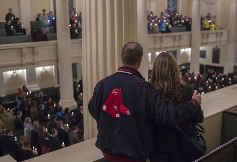 People embrace during a candlelight service at Arlington Church honoring the victims of the Boston Marathon bombings, at the Boston Common in Boston, Massachusetts April 16, 2013. The twin blasts on Monday killed three people including an 8-year-old boy and injured 176 others, some of whom were maimed by bombs packed with ball bearings and nails. (Shannon Stapleton/Reuters photo)