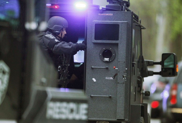 A police SWAT team member prepares to deploy from an armored personnel carrier as multiple armored police vehicles rush down the street during a police assault on a house on Franklin Street during the search for Dzhokhar Tsarnaev. (Jim Bourg/Reuters)