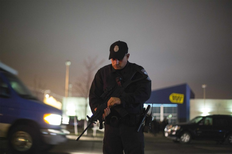 A law enforcement official checks his rifle during a search for the two men suspected of setting off two explosions during the Boston Marathon in Boston, Massachusetts, April 19, 2013. Massachusetts State Police warned people in the Boston suburb of Watertown not to open their doors and said they would conduct a door-to-door, street-by-street search due to what it called a fluid situation. (Lucas Jackson/Reuters)
