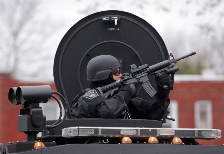A member of the SWAT team trains a gun on an apartment building during a search for the remaining suspect in the Boston Marathon bombings in Watertown, Massachusetts April 19, 2013. Two Boston bomb suspects were named as brothers, Dzhokhar A. Tsarnaev, 19, and his brother Tamerlan Tsarnaev, 26, a U.S. national security official said on Friday. The official said the older brother died in a shootout with police and the younger one was being sought in a house-to-house search for in the Boston suburb of Watertown. (Jessica Rinaldi/Reuters)