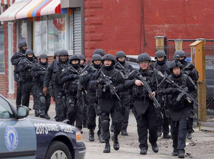 SWAT teams enter a suburban neighborhood to search an apartment for the remaining suspect in the Boston Marathon bombings in Watertown, Massachusetts April 19, 2013. Police killed one suspect in the Boston Marathon bombing during a shootout and were engaged in a house-to-house search for a second man on Friday in the Boston suburb of Watertown after a bloody night of shooting and explosions in the city's streets. (Jessica Rinaldi/Reuters)