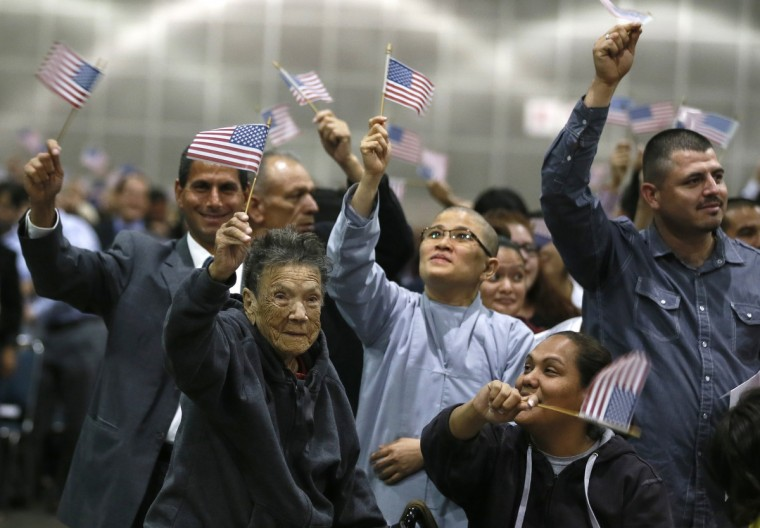 "Ninety-seven-year-old Mercedes Rosa Ruiz Mejia (front L) from Nicaragua joins over 5,000 other immigrants waving U.S. flags after taking the oath of citizenship during a naturalization ceremony to become new citizens of the U.S. in Los Angeles. President Barack Obama on Tuesday embraced a sweeping overhaul of the nation's immigration system put forward by a bipartisan group of senators, saying it was ""largely consistent"" with his own principles for immigration reform. (Lucy Nicholson/Reuters)"