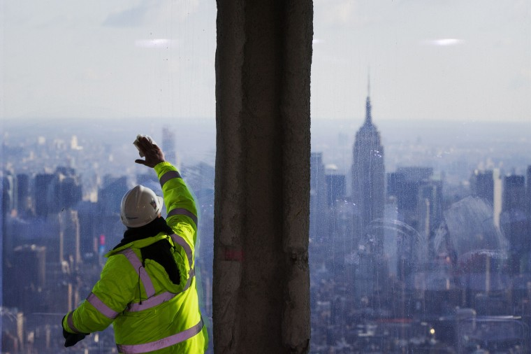 The Empire State Building is visible in the distance as a worker cleans the windows. (Reuters/Lucas Jackson)