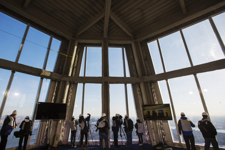 Members of the media take pictures of New York through the windows of the 100th floor observation deck. (Reuters/Lucas Jackson)