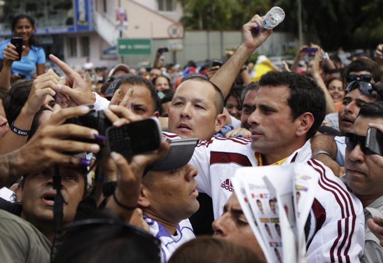 Venezuela's opposition leader and presidential candidate Henrique Capriles (R) arrives to vote for the successor to late President Hugo Chavez, in Caracas April 14, 2013. Venezuelans went to the polls to decide whether to honor Chavez's dying wish for a longtime loyalist to continue his hardline socialism or hand power to a young challenger vowing business-friendly changes. (Christian Veron/Reuters)