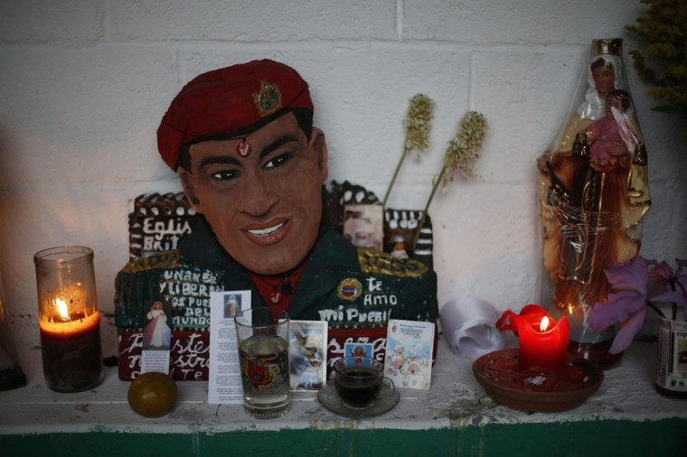 "A figurine of Venezuela's late President Hugo Chavez is seen surrounded by candles and religious images in the ""Saint Hugo Chavez"" altar at the 23 de Enero neighbourhood in Caracas April 12, 2013. Fresh flowers were placed and new candles burning on Sunday at the ""Saint Hugo Chavez"" shrine in Caracas where devotees of the late socialist leader prayed for his last wishes to be fulfilled in the presidential vote. (Tomas Bravo/Reuters)"