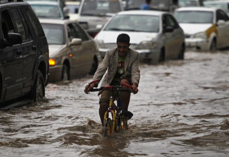 A boy rides his bicycle on a flooded street in Sanaa, Yemen. (Khaled Abdullah/Reuters)