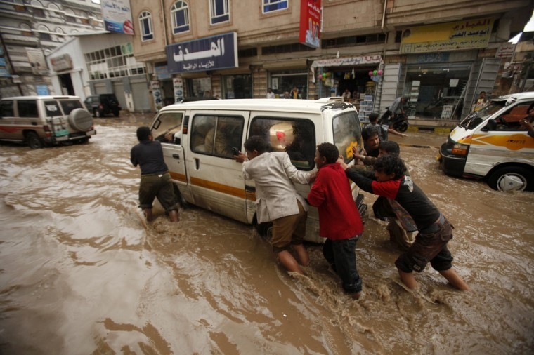 People push a mini-bus stuck on a flooded street after an engine malfunction in Sanaa, Yemen. (Khaled Abdullah/Reuters)
