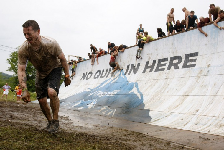 In 2012, a competitor squints as he gets up after trying to run up a half pipe during the Tough Mudder at Mount Snow in West Dover, Vt. The Tough Mudder is a nine mile endurance event which runs competitors through a military style obstacle course complete with mud, water and fire. (Jessica Rinaldi/Reuters)