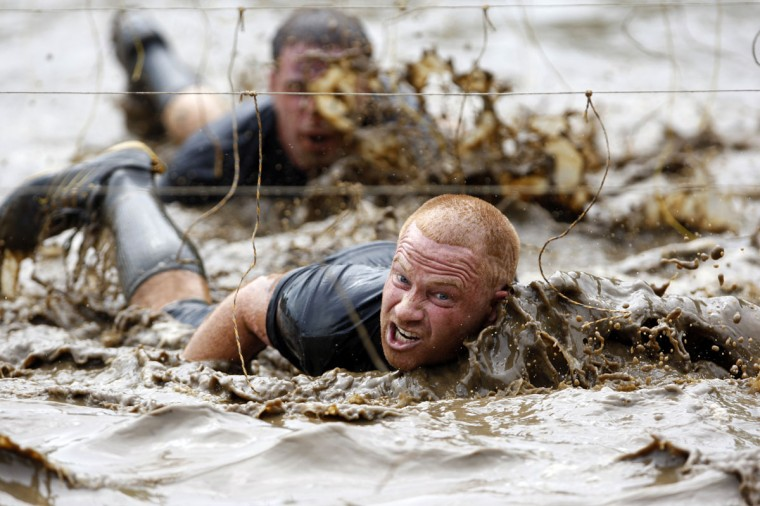 In 2012, competitors swim through mud underneath electrified wires during the Tough Mudder at Mt. Snow in West Dover, Vt. The Tough Mudder is a nine mile endurance event which runs competitors through a military style obstacle course complete with mud, water and fire. (Jessica Rinaldi/Reuters)