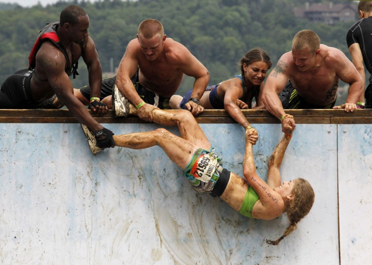In 2012, competitors work to pull a woman up an obstacle where competitors must jump to the top of a half pipe during the Tough Mudder at Mt. Snow in West Dover, Vt. The Tough Mudder is a nine mile endurance event which runs competitors through a military style obstacle course complete with mud, water and fire. (Jessica Rinaldi/Reuters)