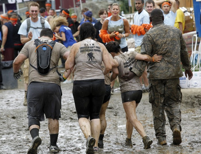 In 2012, competitors embrace as they cross the finish line of the Tough Mudder at Mt. Snow in West Dover, Vt. The Tough Mudder is a nine mile endurance event which runs competitors through a military style obstacle course complete with mud, water and fire. (Jessica Rinaldi/Reuters)