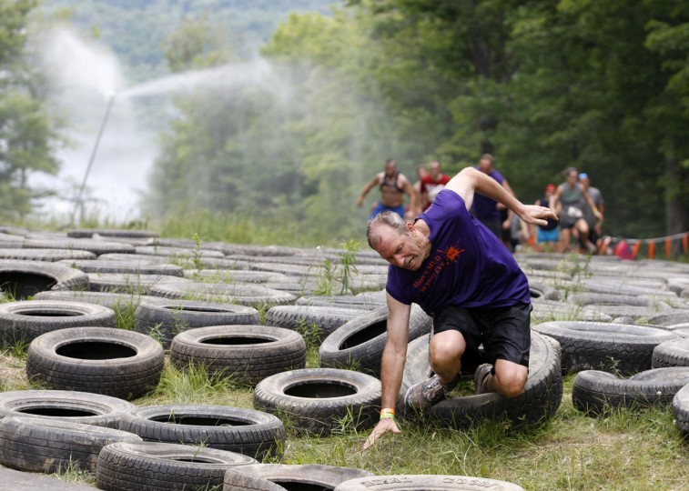 In 2012, a competitor falls as he runs through tires during the Tough Mudder at Mount Snow in West Dover, Vt. The Tough Mudder is a nine mile endurance event which runs competitors through a military style obstacle course complete with mud, water and fire. (Jessica Rinaldi/Reuters)