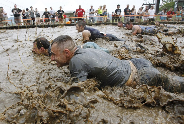 In 2012, competitors crawl through mud underneath electrified wires during the Tough Mudder at Mt. Snow in West Dover, Vt. The Tough Mudder is a nine mile endurance event which runs competitors through a military style obstacle course complete with mud, water and fire. (Jessica Rinaldi/Reuters)