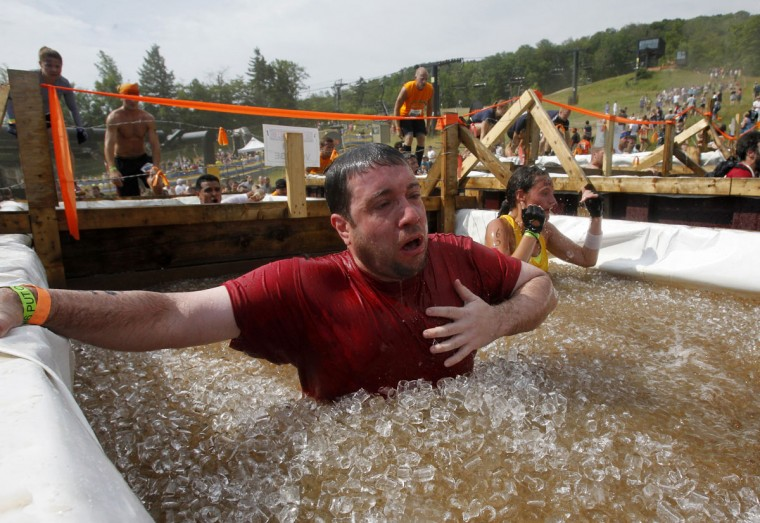 In 2012, a competitor reacts after jumping into a vat of ice water during the Tough Mudder at Mount Snow in West Dover, Vt. The Tough Mudder is a nine mile endurance event which runs competitors through a military style obstacle course complete with mud, water and fire. (Jessica Rinaldi/Reuters)