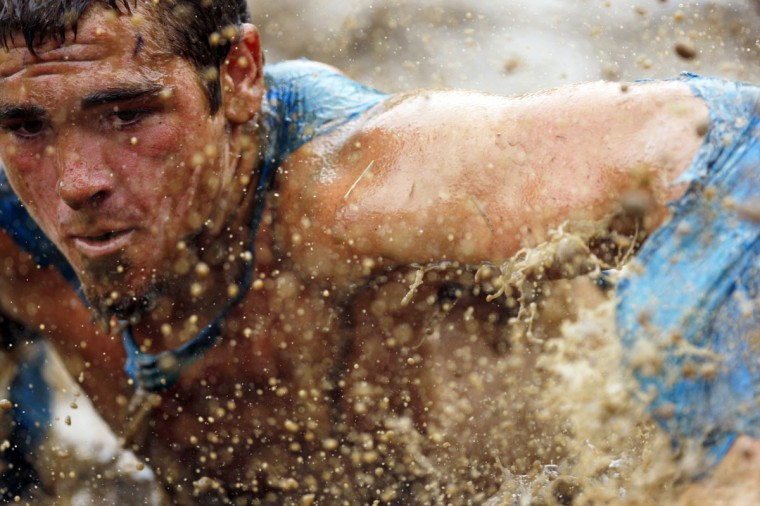 In 2012, mud flies in front of a competitor as he swims through mud underneath electrified wires during the Tough Mudder at Mt. Snow in West Dover, Vt. The Tough Mudder is a nine mile endurance event which runs competitors through a military style obstacle course complete with mud, water and fire. (Jessica Rinaldi/Reuters)