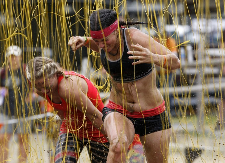 In 2012, competitors react as they run through electrified wires before crossing the finish line of the Tough Mudder at Mt. Snow in West Dover, Vt. The Tough Mudder is a nine mile endurance event which runs competitors through a military style obstacle course complete with mud, water and fire. (Jessica Rinaldi/Reuters)