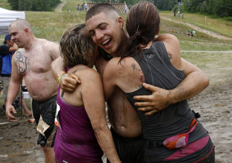 In 2012, competitors embrace after crossing the finish line in the Tough Mudder at Mt. Snow in West Dover, Vt. The Tough Mudder is a nine mile endurance event which runs competitors through a military style obstacle course complete with mud, water and fire. (Jessica Rinaldi/Reuters)