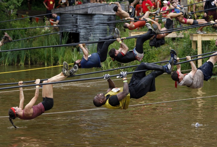 In 2012, competitors pull themselves over water along a rope during the Tough Mudder at Mt. Snow in West Dover, Vt. The Tough Mudder is a nine mile endurance event which runs competitors through a military style obstacle course complete with mud, water and fire. (Jessica Rinaldi/Reuters)