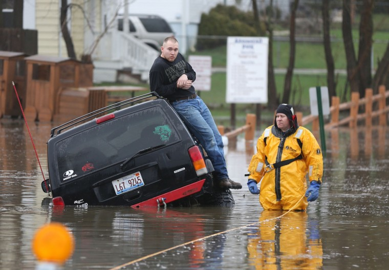 A rescue official stands with a motorist stuck in water during heavy rains and flooding in Round Lake Heights, Illinois, Thursday, April 18, 2013, at Pontiac Court and Tomahawk Trail. (Joe Shuman/Chicago Tribune/MCT)