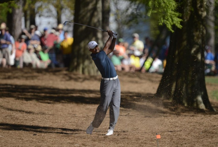 Tiger Woods hits out of the pine straw on the 13th hole during the third round of the 2013 The Masters golf tournament at Augusta National Golf Club. (Jack Gruber/USA TODAY Sports)