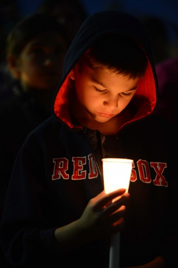 Benjamin McCormick looks into his candle during a vigil at Garvey Park in Dorchester, near the home of Marathon bombing victim Martin Richard, 8. (Michael Ivins/USA TODAY Sports)