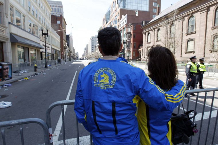 Ned Beatty and Kimberley Beatty from San Diego comfort each other as they look down Boyston Street towards the finish area the day after a bombing near finish line of the 2013 Boston Marathon. (Greg M. Cooper/USA TODAY Sports)