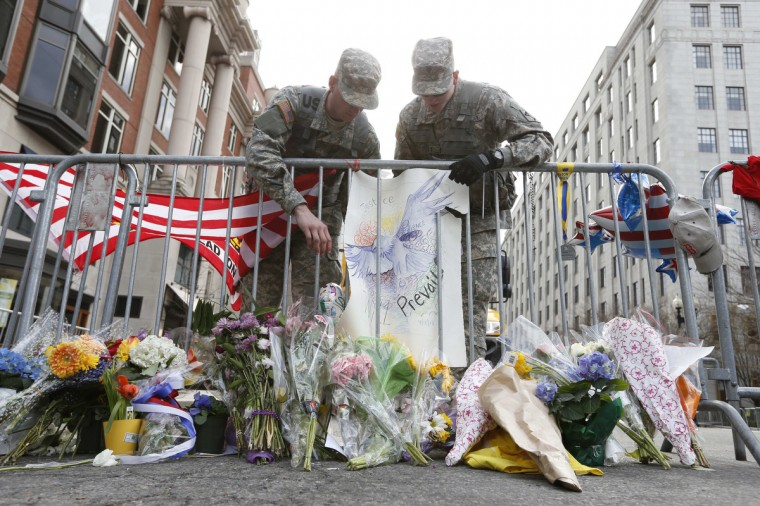 Military personnel adjust a sign at the intersection of Berkeley and Boylston Street the day after a bombing near finish line of the 2013 Boston Marathon. (Greg M. Cooper/USA TODAY Sports)