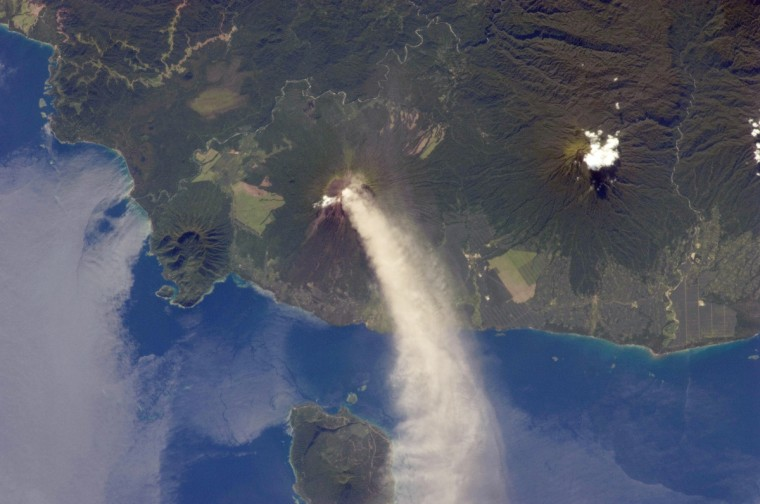 Numerous volcanoes contribute to the landmass of the island of New Britain, the largest in the Bismarck Archipelago of Papua New Guinea. One of the most active of these volcanoes - Ulawun - is also the tallest, with a summit elevation of 2,334 meters (7,657 feet). This astronaut photograph was taken during the most recent phase of volcanic activity at Ulawun. A plume of white steam and ash extends from the summit crater of the stratovolcano towards the northwest. The plume begins to broaden as it passes the southwestern coast of Lolobau Island, approximately 23 kilometers downwind. Note that the image is oriented such that north is towards the lower left. NASA image