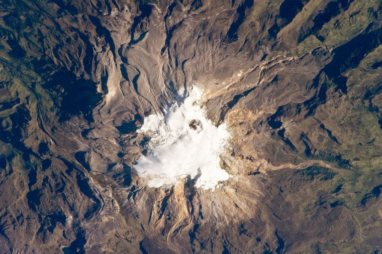 Nevado del Ruiz Volcano (image center) is located approximately 140 kilometers (87 miles) to the northwest of Colombia's capital, Bogot‡. Covering over 200 square kilometers (77 square miles), Nevado del Ruiz is a large stratovolcano - a cone-shaped volcano built from successive layers of lava, ash, and pyroclastic flow deposits. The volcano is fed by magma generated above the boundary between the subducting Nazca and overriding South American tectonic plates. The historical record of eruptions at the volcano extends back to 1570, but the most damaging eruption in recent times took place in 1985. On the November 13, 1985, an explosive eruption at the Arenas Crater (image center) melted ice and snow at the summit of the volcano. Mudflows (lahars) swept tens of kilometers down river valleys along the volcano's flanks, killing at least 23,000 people. Most of the fatalities occurred in the town of Armero which was completely inundated by lahars. Eruptive activity at Nevado del Ruiz may have occurred in 1994, but this is not confirmed. NASA image