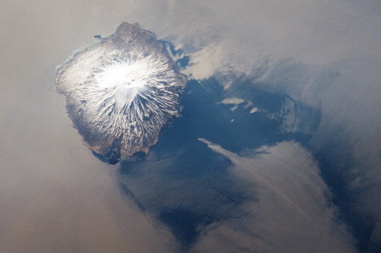 The Kuril Island chain extends from the Kamchatka Peninsula to Japan and contains numerous active volcanoes along its length. This astronaut photograph highlights Alaid Volcano, the highest (2,339 meters above sea level) volcano in the chain, as well as the northernmost. The textbook cone-shaped morphology of this stratovolcano is marred only by the summit crater, which is breached to the south (image center) and highlighted by snow cover. The volcano rises 3000 meters from the floor of the Sea of Okhotsk, with the uppermost part of the volcano exposed as an island. NASA image