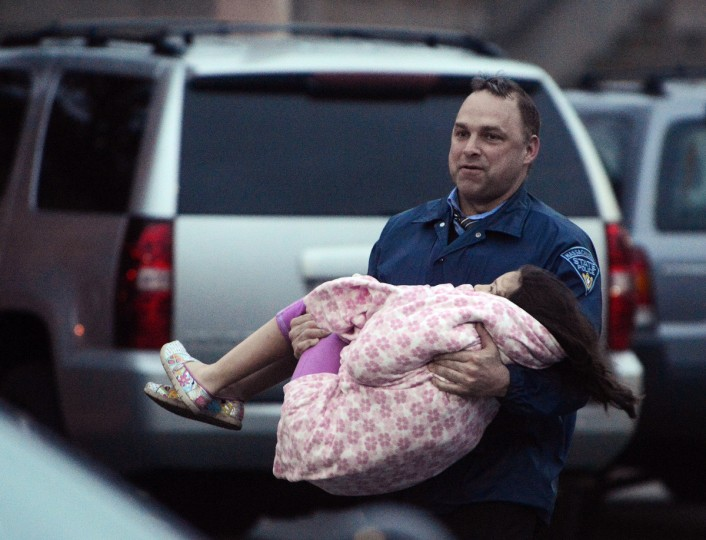 An officer carries a child away from an area where a suspect is hiding on Franklin St., on April 19, 2013 in Watertown, Massachusetts. (Darren McCollester/Getty Images)