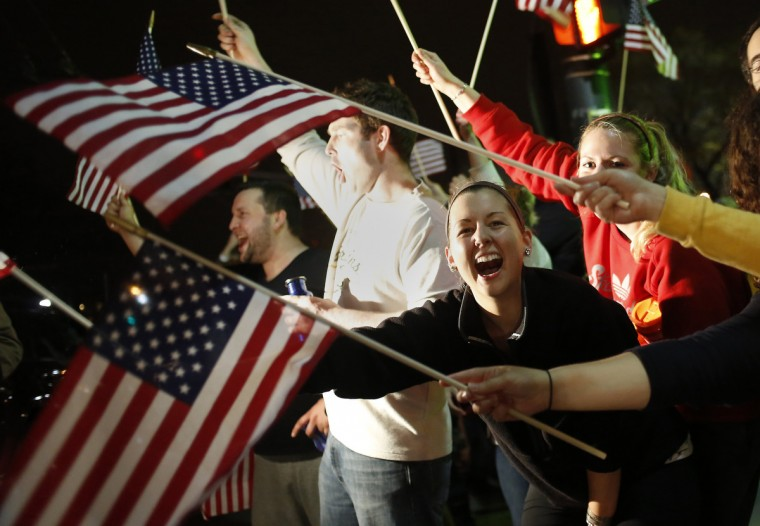 People wave U.S. flags while cheering as police drive down Arlington street in Watertown, Massachusetts April 19, 2013. The second suspect in the Boston Marathon bombing, Dzhokhar Tsarnaev, 19, was bleeding, seriously injured and being treated at a Massachusetts hospital on Friday after he was found hiding in a boat, state police said. (Shannon Stapleton/Reuters)